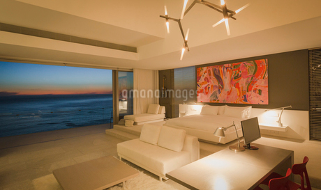 Illuminated modern, luxury home showcase interior bedroom with ocean view at duskの写真素材 [FYI02180781]