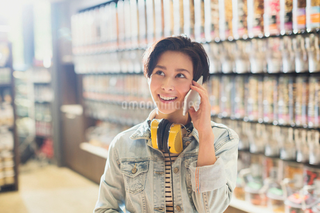 Smiling young woman with headphones talking on cell phone in grocery store marketの写真素材 [FYI02180783]