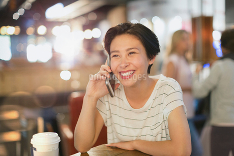Smiling young woman talking on cell phone in cafeの写真素材 [FYI02180788]