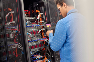 Male IT technician performing diagnostics on panel in server roomの写真素材 [FYI02180818]