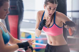 Determined, tough young female boxer shadowboxing in gymの写真素材 [FYI02180832]
