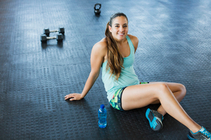 Portrait smiling, confident young woman resting post workout in gymの写真素材 [FYI02180872]