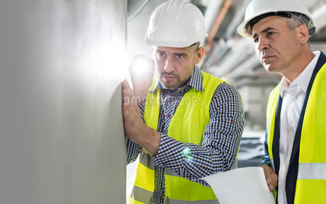 Male engineer with flashlight examining underground wall at construction siteの写真素材 [FYI02180878]
