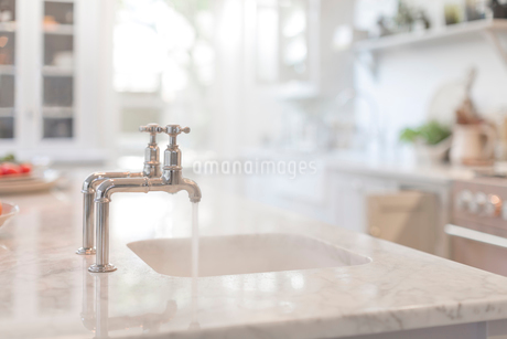 Water running from faucet in kitchen sinkの写真素材 [FYI02180880]