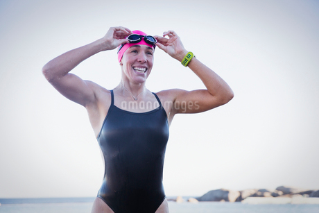 Smiling, confident female open water swimmer adjusting swimming gogglesの写真素材 [FYI02180907]