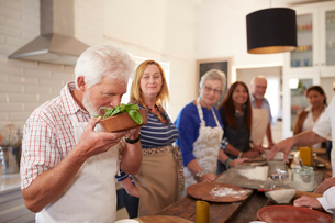 Active senior friends taking cooking class, smelling fresh basilの写真素材 [FYI02180928]