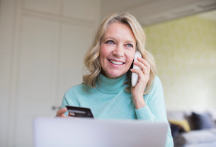 Smiling mature woman with credit card talking on telephone at laptopの写真素材 [FYI02180935]