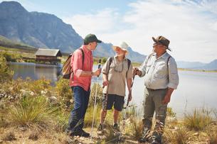 Active senior men friends hiking along sunny summer lakeの写真素材 [FYI02180993]