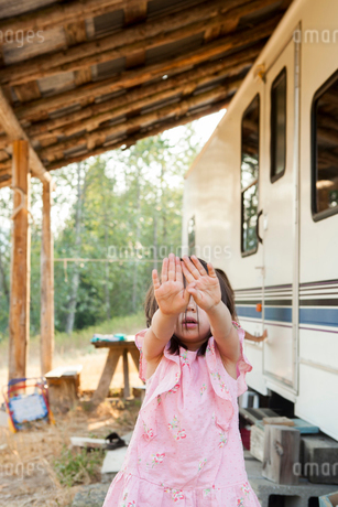 Portrait shy girl hiding face with hands outside rural camperの写真素材 [FYI02181036]