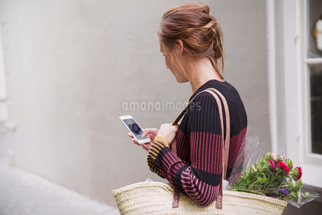 Woman video chatting with cell phone in alleyの写真素材 [FYI02181047]