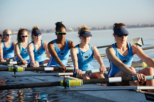 Female rowers rowing scull on sunny lakeの写真素材 [FYI02181050]