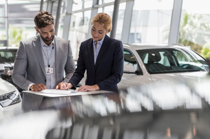 Car salesman watching female customer signing financial contract paperwork in car dealership showrooの写真素材 [FYI02181064]