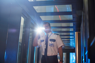 Male security guard with flashlight in server roomの写真素材 [FYI02181078]