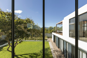 View from windows of sunny modern luxury home showcase exterior with yard and treeの写真素材 [FYI02181109]