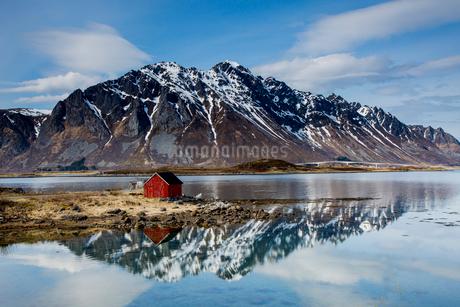 Remote fishing hut at fjord waterfront below craggy mountains, Kleppstad, Austvagoya, Norwayの写真素材 [FYI02181116]