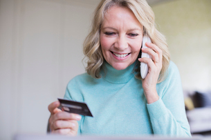Smiling mature woman with credit card talking on telephoneの写真素材 [FYI02181120]