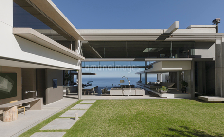 Sunny modern, luxury home showcase exterior courtyard and houseの写真素材 [FYI02181124]