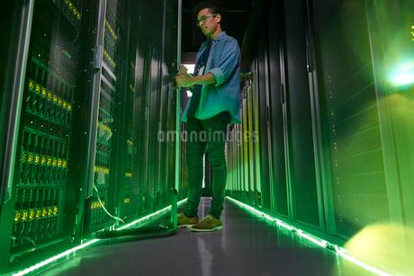 Male IT technician working in dark server room with glowing green panelsの写真素材 [FYI02181130]