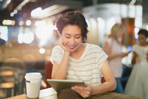 Young woman using digital tablet and drinking coffee in cafeの写真素材 [FYI02181132]