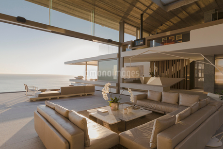 Sunny modern, luxury home showcase interior living room open to ocean viewの写真素材 [FYI02181173]
