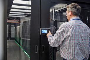 Male IT technician inputting security code at server room access doorの写真素材 [FYI02181197]