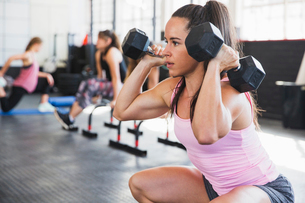Determined, muscular young woman doing squats with dumbbells in gymの写真素材 [FYI02181258]