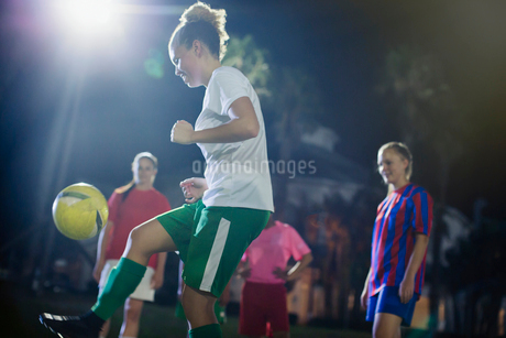 Young female soccer player kicking the ball, practicing on field at nightの写真素材 [FYI02181272]
