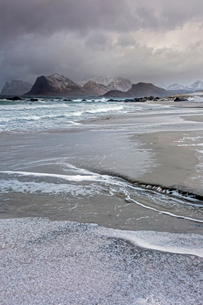 Rugged mountains behind cold, ocean beach tide, Storsandnes, Lofoten, Norwayの写真素材 [FYI02181284]