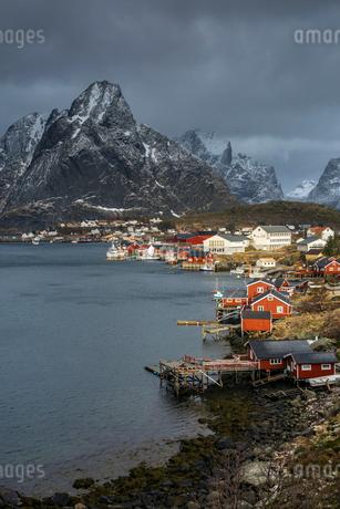 Fishing village at waterfront below rugged mountains, Reine, Lofoten, Norwayの写真素材 [FYI02181297]