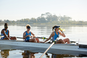 Female rowing team resting, drinking water in scull on sunny lakeの写真素材 [FYI02181319]