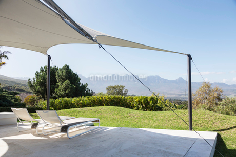 Lounge chairs under awning on sunny patio with mountain viewの写真素材 [FYI02181321]