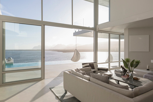 Sunny, tranquil modern luxury home showcase interior living room with ocean viewの写真素材 [FYI02181326]