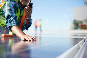 Engineer with walkie-talkie inspecting solar panels at power plantの写真素材 [FYI02181352]