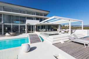 Sunny modern luxury home showcase exterior with lounge chairs and swimming poolの写真素材 [FYI02181441]