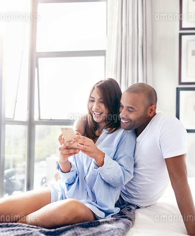 Smiling couple texting with cell phone on bedの写真素材 [FYI02181466]