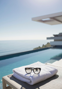Sunglasses on folded towel at poolside on sunny luxury patio with ocean viewの写真素材 [FYI02181472]