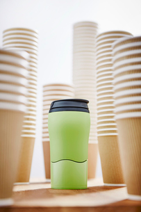 Green insulated drink container surrounded by disposable coffee cupsの写真素材 [FYI02181478]