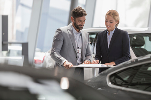 Car salesman and female customer reviewing financial contract paperwork in car dealership showroomの写真素材 [FYI02181509]