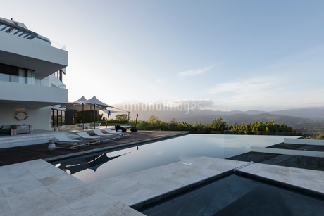 Tranquil modern luxury home showcase exterior with infinity pool and mountain viewの写真素材 [FYI02181515]