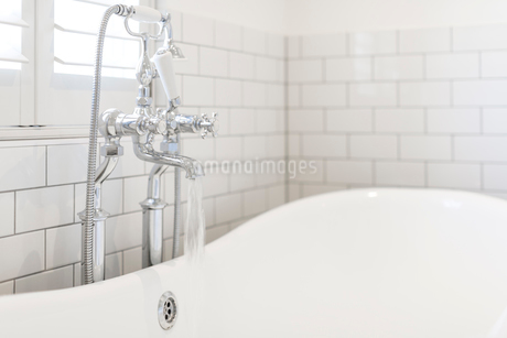 Water running from bathroom faucet into white soaking tubの写真素材 [FYI02181525]
