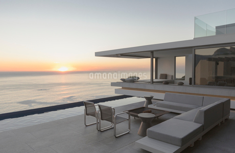 View of sunset over ocean horizon from modern, luxury home showcase exterior patioの写真素材 [FYI02181576]