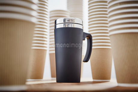 Insulated drink container surrounded by disposable coffee cupsの写真素材 [FYI02181609]