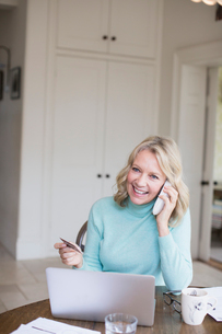 Smiling mature woman with credit card talking on telephone at laptopの写真素材 [FYI02181639]