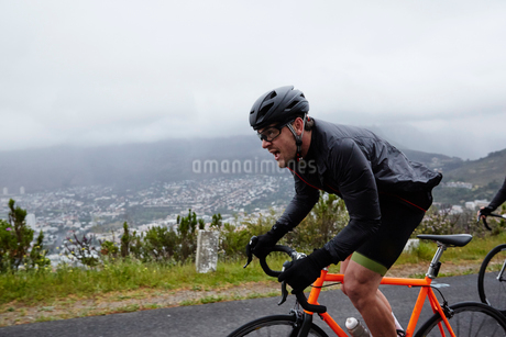 Determined male cyclist cycling on rainy roadの写真素材 [FYI02181700]