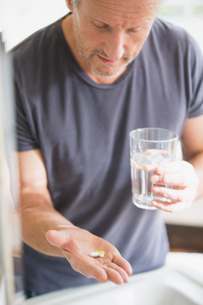 Mature man taking vitamins with glass of waterの写真素材 [FYI02181735]