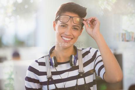Portrait confident creative businesswoman with headphones and eyeglassesの写真素材 [FYI02181757]