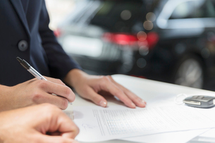 Close up customer signing financial contract paperwork in car dealershipの写真素材 [FYI02181778]