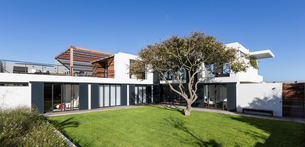 Sunny modern luxury home showcase exterior with yard and treeの写真素材 [FYI02181807]