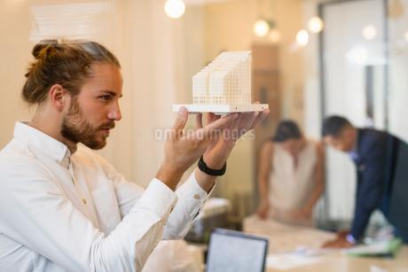 Focused, curious male architect examining modelの写真素材 [FYI02181879]