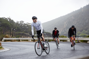 Male cyclists cycling uphill on wet roadの写真素材 [FYI02181906]